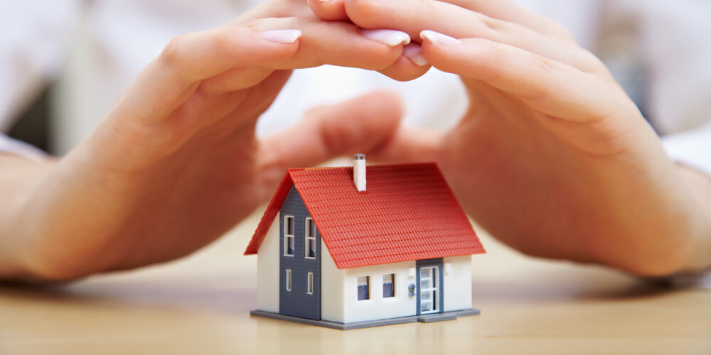 hands protecting toy house Security from Hodson Developments