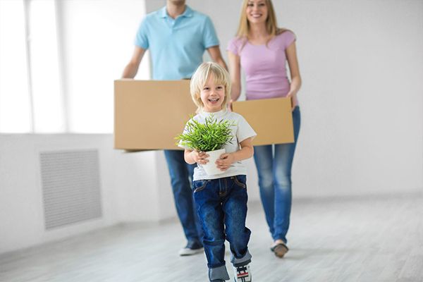Child holding plant and adults holding boxes for new build home